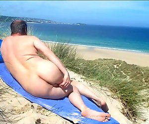 Male nudist spied massaging his butt, genitals in the dunes